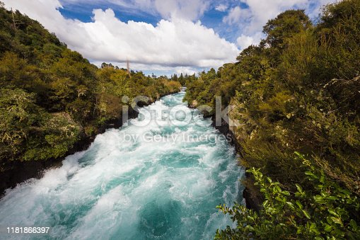 Huka Falls, clear blue water flowing fast though the forrest.