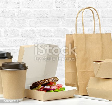 istock Fast food and drink packaging with freshly prepared Sandwich with bacon, tomato, cucumber, on whole grain wheat toast 1048502714