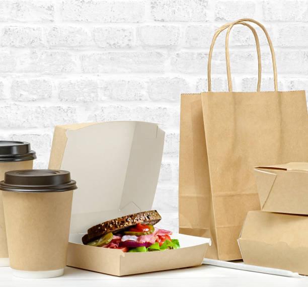 fast food and drink packaging with freshly prepared sandwich with bacon, tomato, cucumber, on whole grain wheat toast - karton zbiornik zdjęcia i obrazy z banku zdjęć