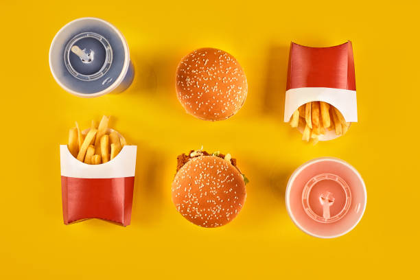 Fast food and unhealthy eating concept - close up of fast food snacks and cold drink on yellow background stock photo
