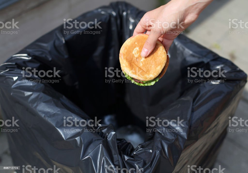 Fast food and unhealthy eating concept - hand throwing a burger in the trash on street stock photo