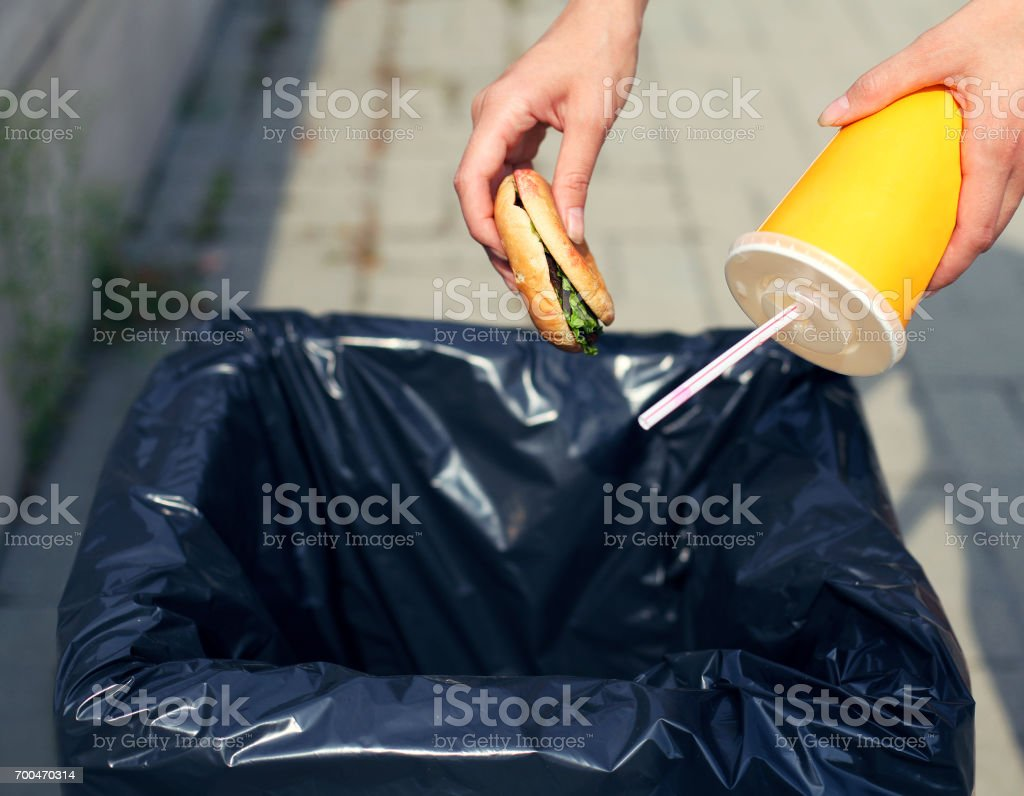 Fast food and unhealthy eating concept - hand throwing a burger with a plastic cup in the trash on the street city stock photo
