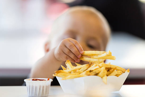 Fast Food Baby Baby boy trying to grab french fries eastern european descent stock pictures, royalty-free photos & images