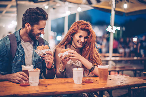Fast food date A young couple having snack and drink at an outdoors music festival. Eating burgers with fries and drinking beer. date night romance stock pictures, royalty-free photos & images