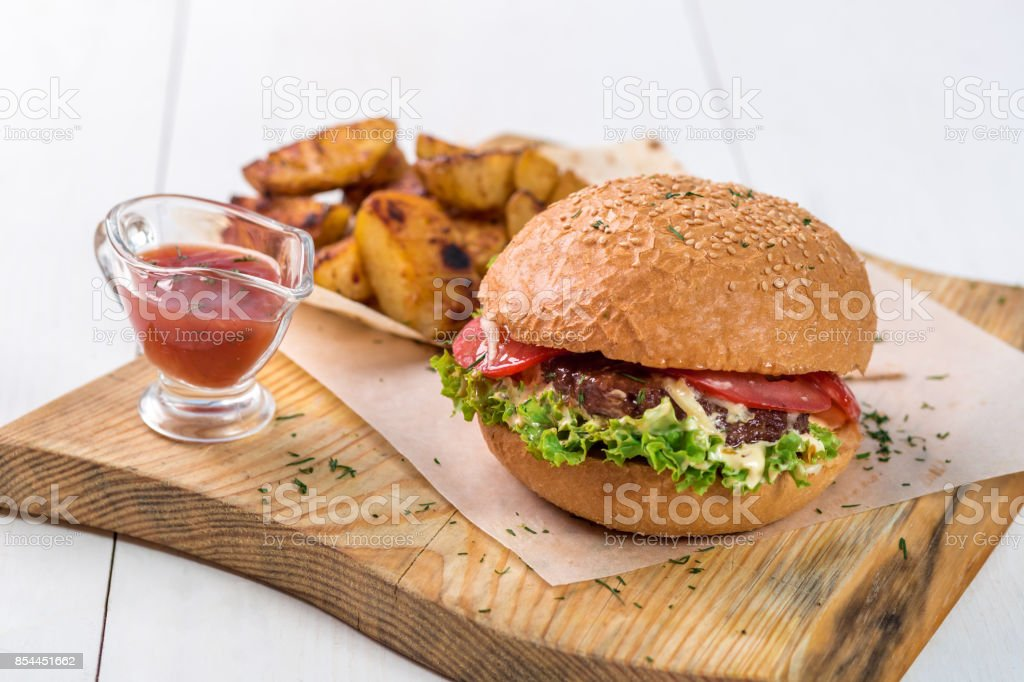 Fast food dish. Appetizing meat burger, potato chips and sauce. Takeaway composition stock photo