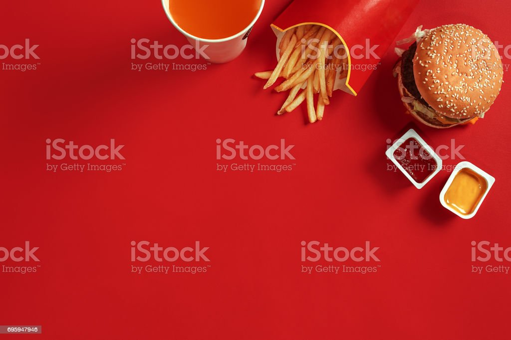 Fast food dish top view. Meat burger, potato chips and glass of drink on red background. Takeaway composition stock photo