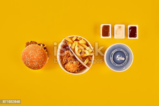 1134487598 istock photo Fast food dish top view. Meat burger, potato chips and wedges. Take away composition. French fries, hamburger, mayonnaise and ketchup sauces on yellow background 871952846