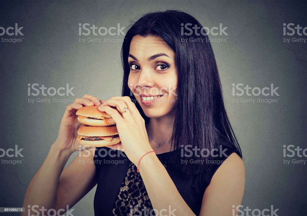 Fast food is my favorite. Woman eating a double cheeseburger enjoying the taste stock photo