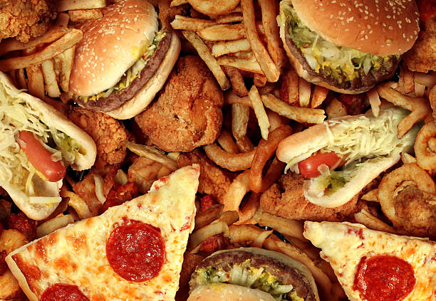 Fast food items like hot dogs, hamburgers, fries and pizza Fast food concept with greasy fried restaurant take out as onion rings burger and hot dogs with fried chicken french fries and pizza as a symbol of diet temptation resulting in unhealthy nutrition. unhealthy eating stock pictures, royalty-free photos & images