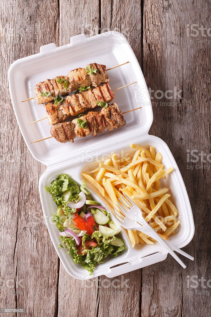 Fast food: kebabs, fries and fresh salad in tray. vertical stock photo