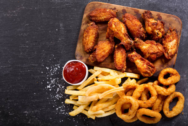 fast food meals : onion rings, french fries and fried chicken - жареный стоковые фото и изображения