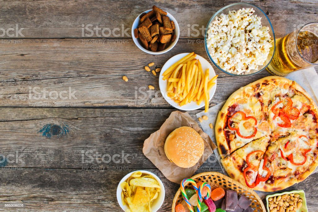 Fast food on old wooden background. Concept of junk eating. Top view. stock photo