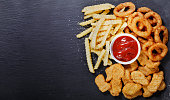 istock fast food products: onion rings, french fries and chicken nuggets 1090835110