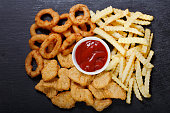 istock fast food products: onion rings, french fries and chicken nuggets 1090835116