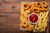 istock fast food products: onion rings, french fries and chicken nuggets 1090835122