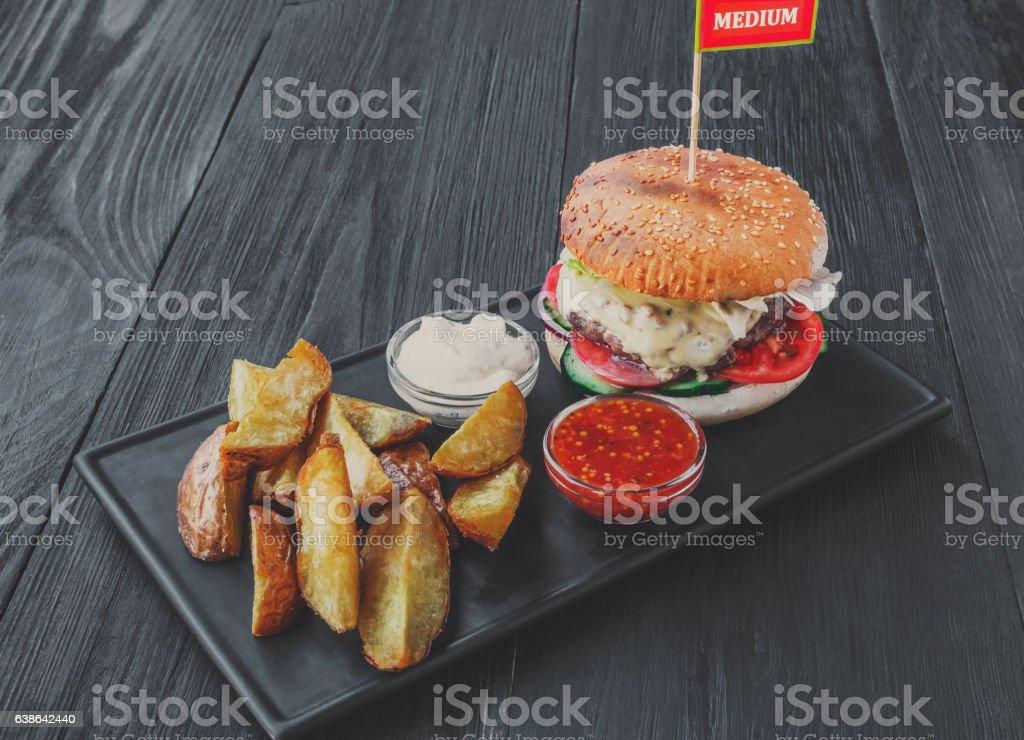 Fast food restaurant dish on served table. Meat steak medium rare in...