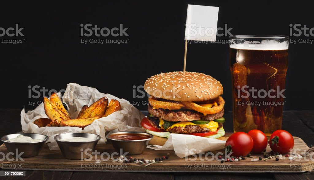 Fast food restaurant dish. Hamburger and fries wedges royalty-free stock photo
