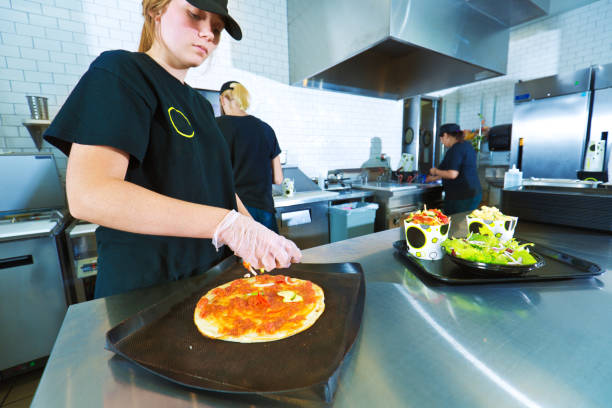 fast food restaurant young kitchen staff worker preparing convenience food - fast food restaurant stock pictures, royalty-free photos & images