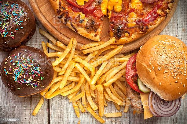 Closeup of home made burgers , french fries and donuts on wooden background