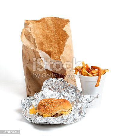 Classic fast food; a cheeseburger and french fries in a cup. Isolated on a white background. Focus is on the front of the cheeseburger.