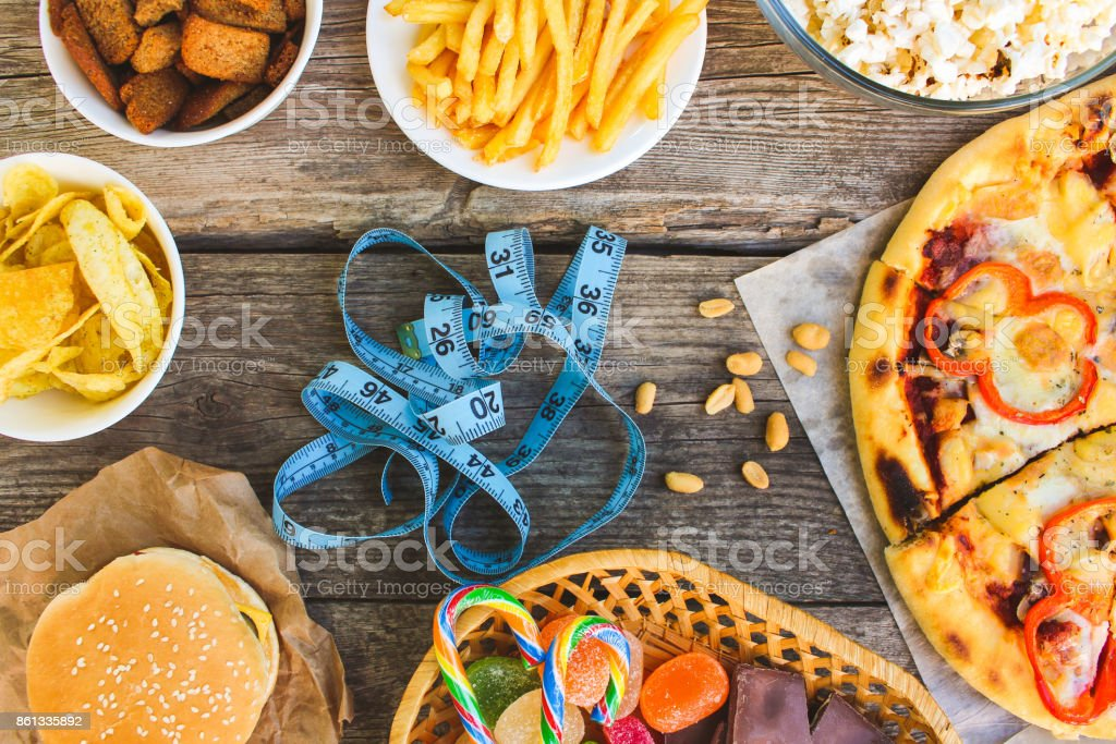 Fast food, tape measure on old wooden background. Concept of junk eating. Toned image. Top view. stock photo