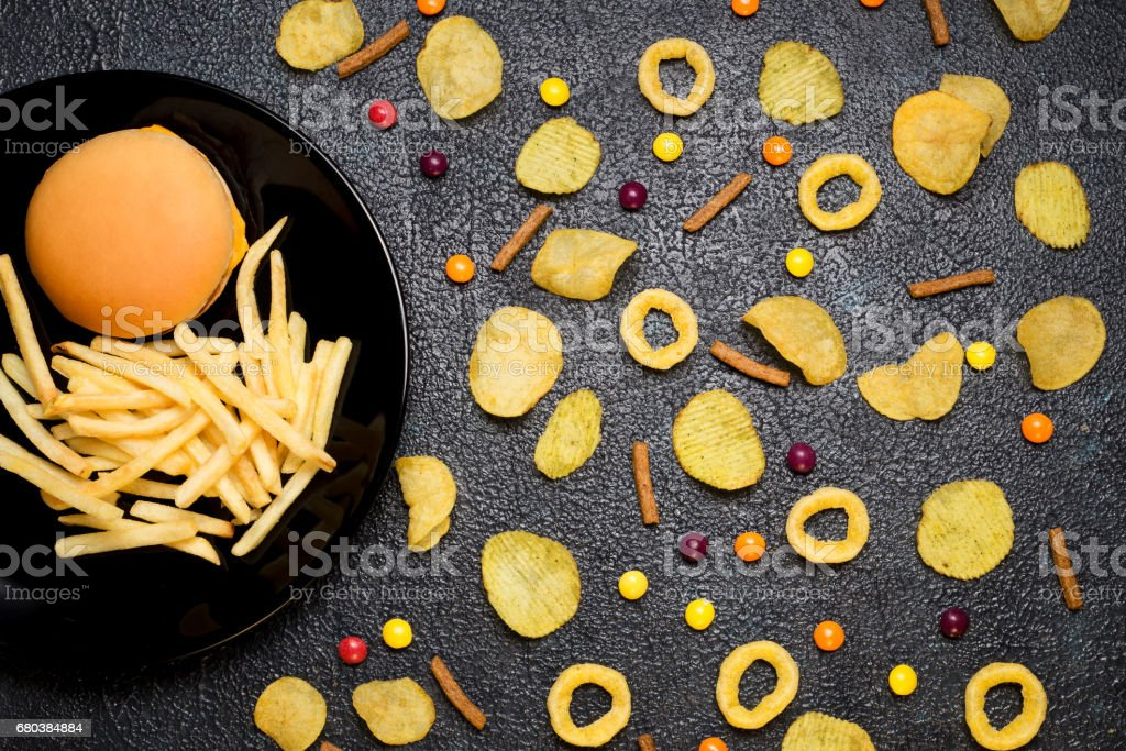 Fast food: top view of burger, french fries, chips, rings and candies. Unhealthy eating concept royalty-free stock photo