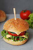 Fast food. Vegetarian Homemade Burger Cheese, Cucumber, Tomato and Lettuce, Salad. Tasty Sandwich for lunch Fresh Vegetables. Gray Textured Table