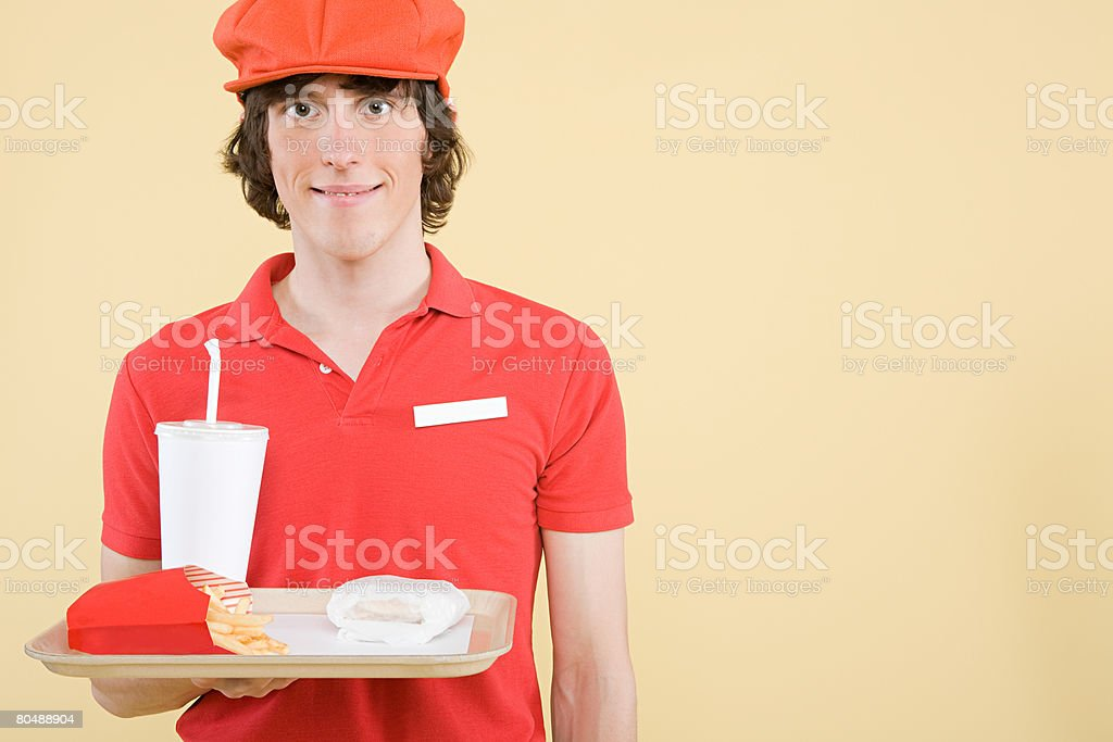 A fast food worker holding a tray of food royalty-free 스톡 사진