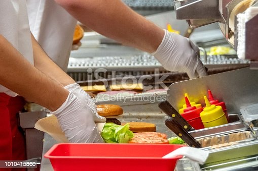 Fast food workers working in a hamburger restaurant close up