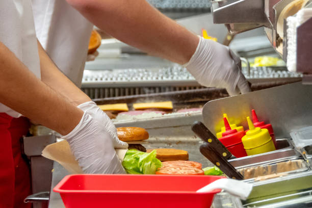 fast food workers working in a hamburger restaurant - fast food restaurant stock pictures, royalty-free photos & images