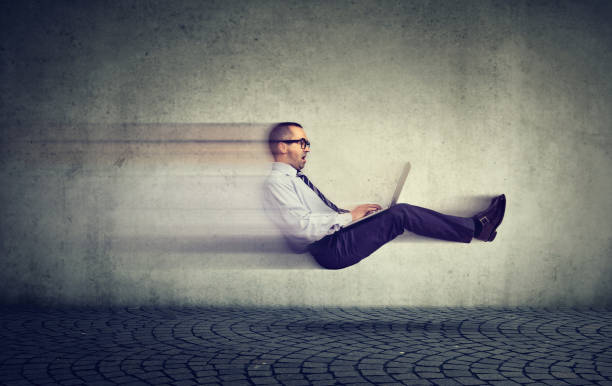 Fast internet concept. Levitating business man on road using laptop stock photo