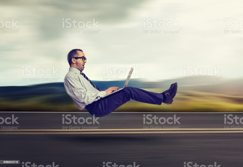 Fast internet concept. Levitating business man on road using laptop computer'n stock photo