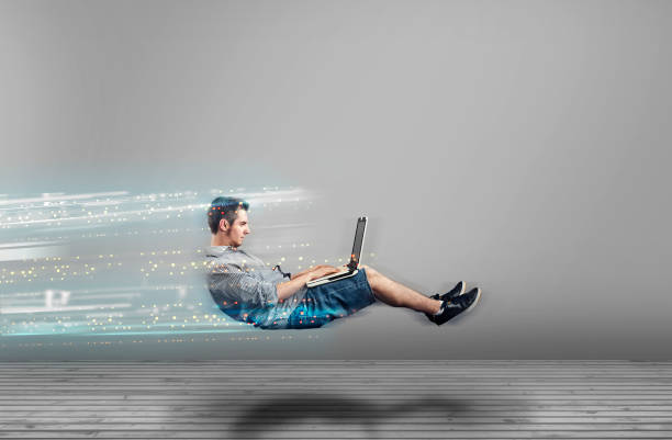 fast levitating man in a white room using a laptop. high speed browsing. - velocidade imagens e fotografias de stock
