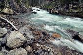 Mountain river flowing through the narrow rocky gorge