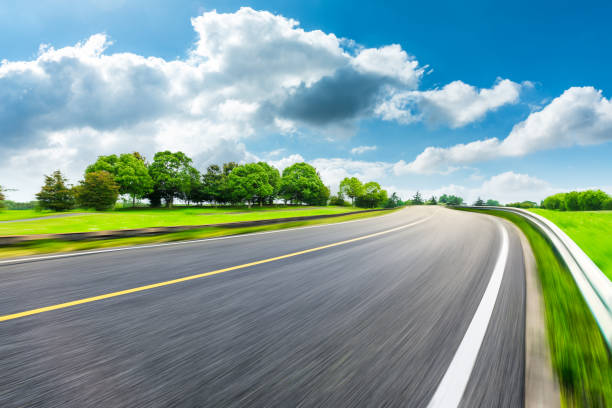 Fast moving asphalt road and green forest landscape. stock photo