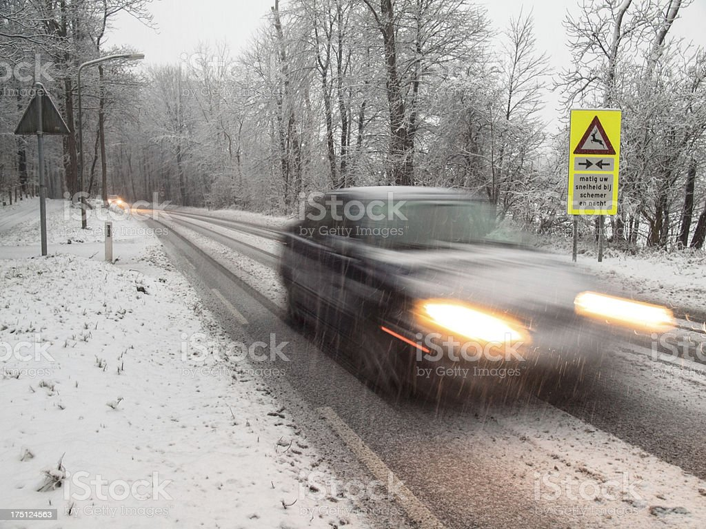 fast moving car brakes in a snow storm stock photo