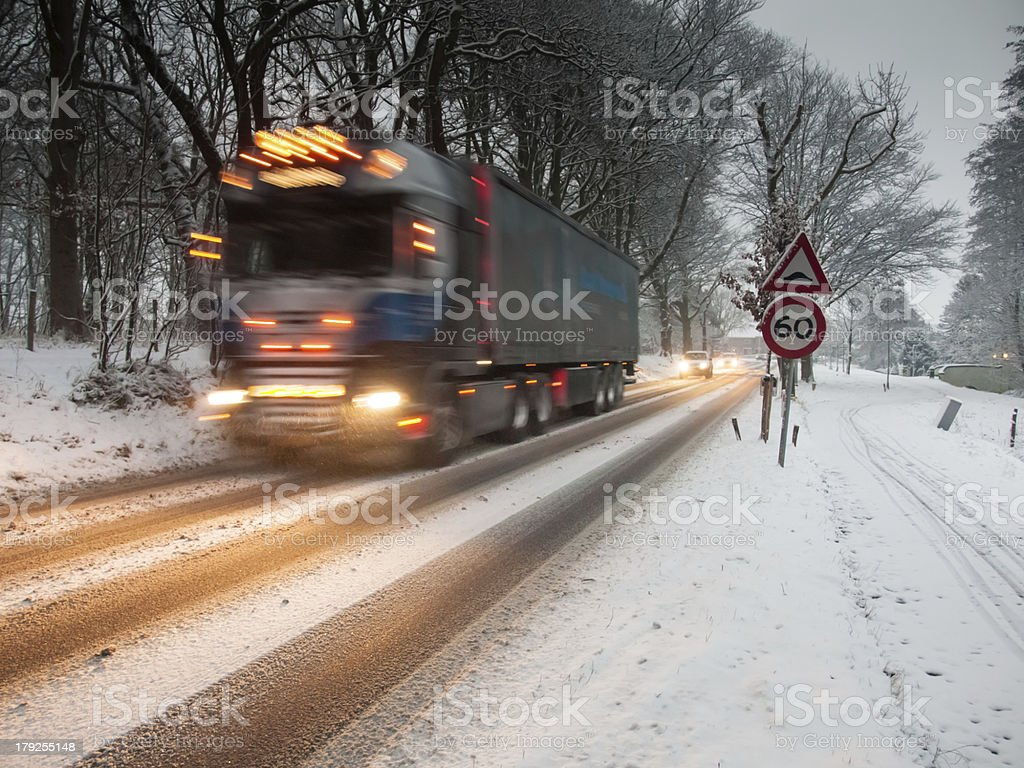 fast moving heavy goods vehicle in a snow storm stock photo