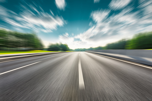 Fast moving asphalt road and green forest landscape.
