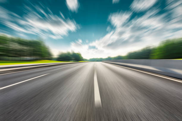Fast moving road and green forest landscape. stock photo