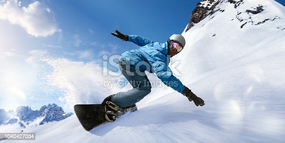 A close up image of a black snowboarder laying into a carve turning the snowboard towards the camera. The snowboarder is dressed in blue jacket, salopettes, helmet and visor and is travelling at high speed down a slope with snow spraying out from behind the board. With motion blur.
