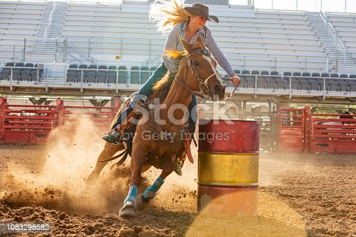 Fast paced action of cowgirls competing in the barrel riding event at a rodeo