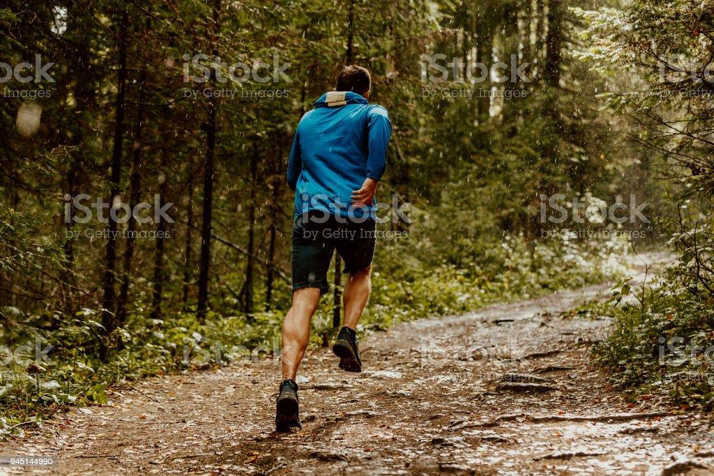 fast running athlete runner forest trail under rain stock photo