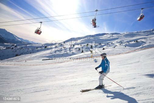 Very fast ski driver in front of the mountains at a sunny day. The photo was taken at Alp St