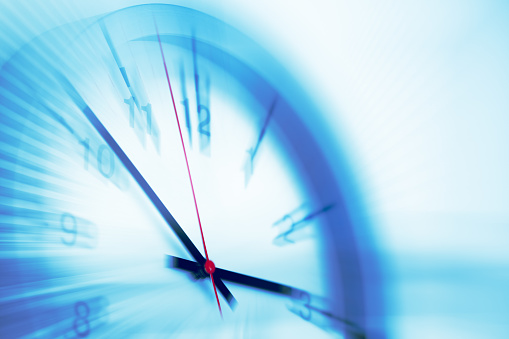 Silver colored stopwatch in front of blue wall. Horizontal composition with copy space.