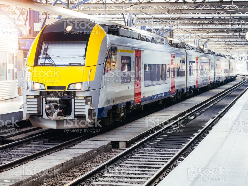 Fast train departing from train station in big city - transportation for commuters and local travelers stock photo