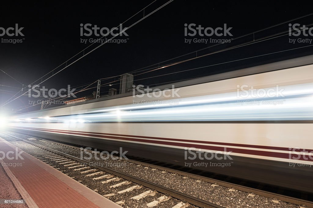 Fast train passing through a railway station at night stock photo