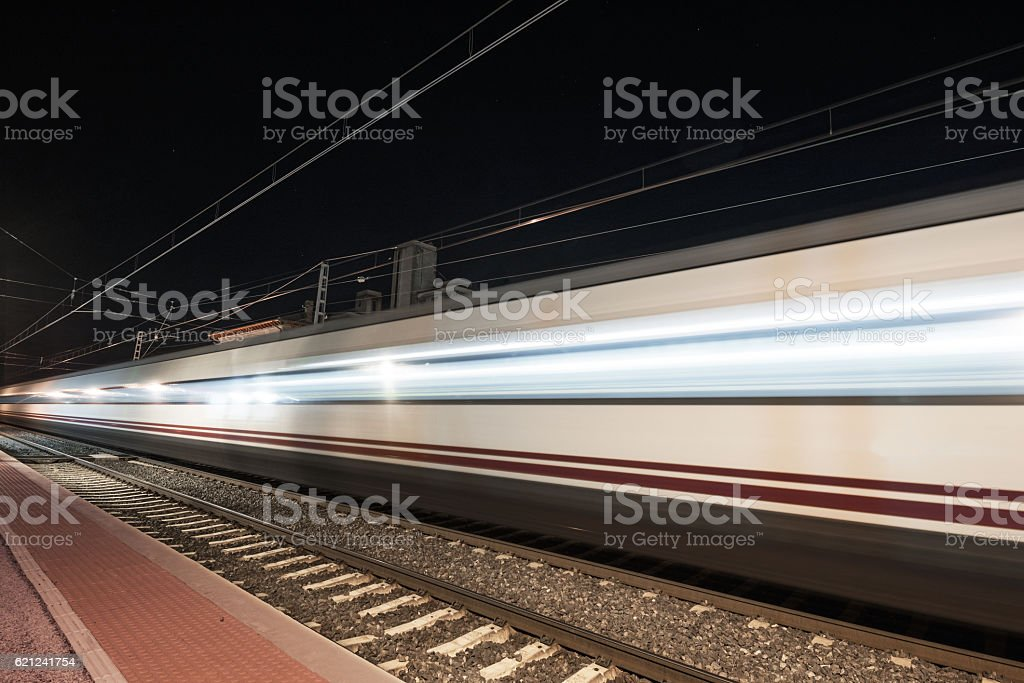 Fast train passing through a station at night stock photo