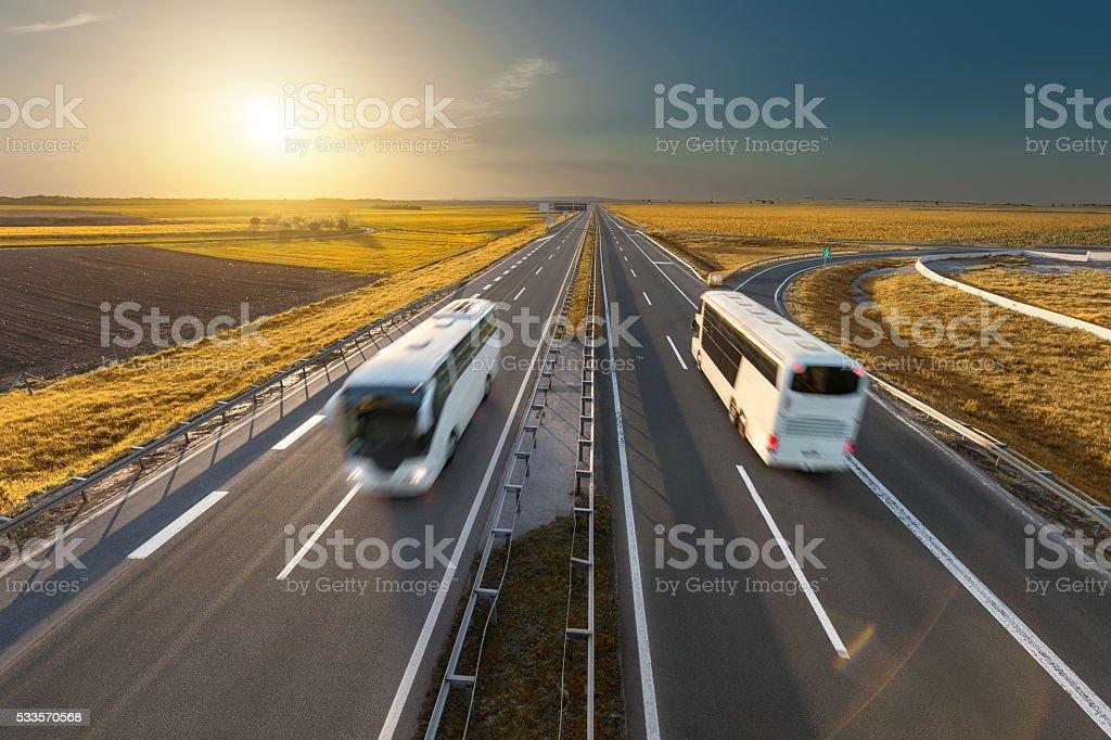 Rápido de viaje de autobuses en la carretera en el idílico atardecer - foto de stock