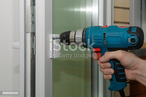 966792200 istock photo fastening the handle to the plastic door with electric screwdriver 898966930