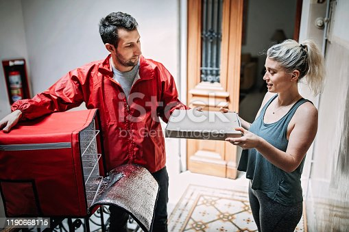 Mid adult male delivery person giving Pizza box to attractive   woman at doorstep